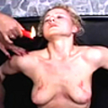 Mistress applies hot wax and dildo to slave cunt